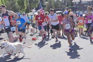 Runners and their dogs take off at the start of the Dog Gone Run.